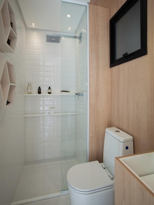 Banheiro com prateleiras e nichos organizadores.