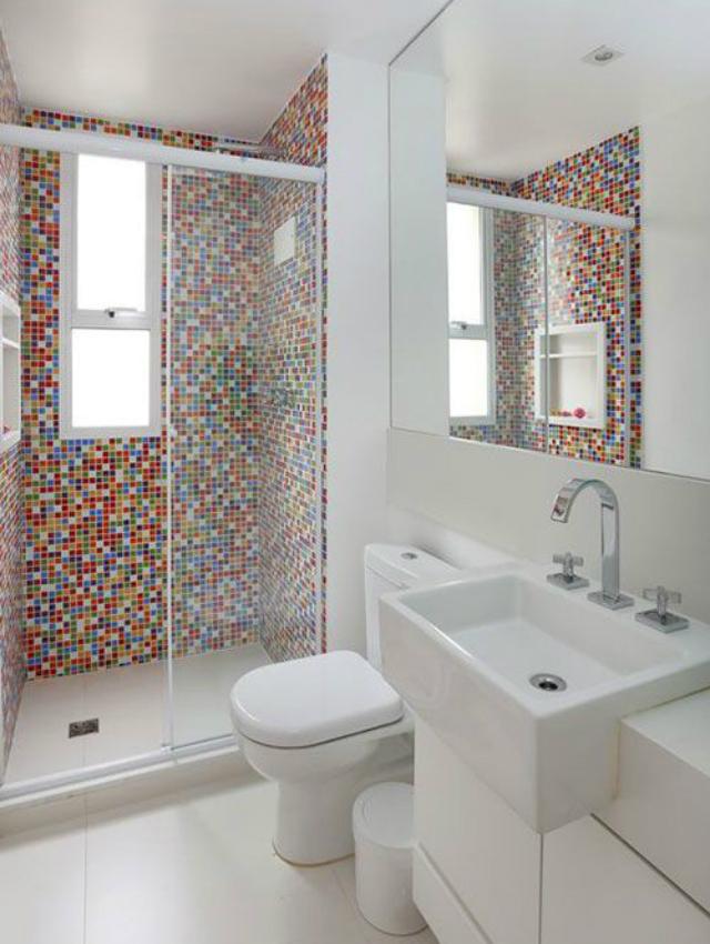 Banheiro todo branco com paredes de dentro do box revestidas de pastilhas coloridas.