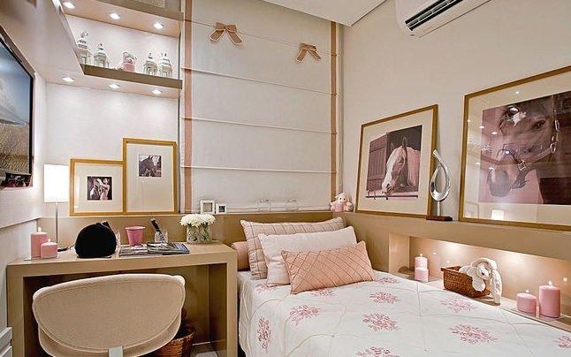 Decoração de apartamento pequeno com nicho iluminado e quadros no quarto.