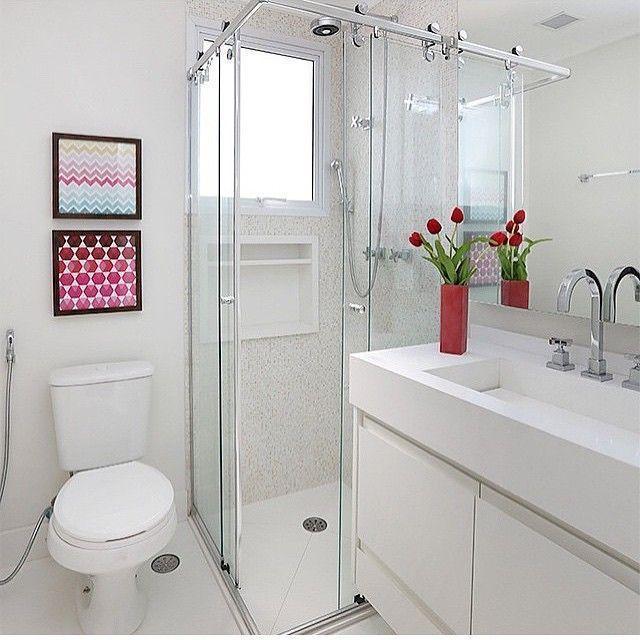 Decoração de banheiro pequeno com quadros coloridos e vaso de flores na pia.