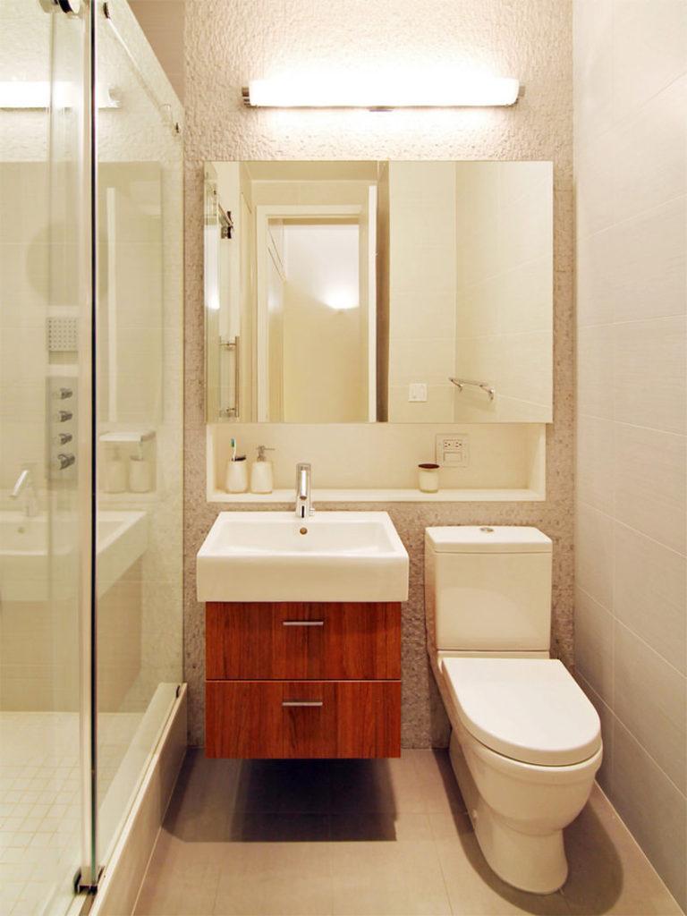 Parede de banheiro com revestimento com textura, nicho branco embutido e espelho.