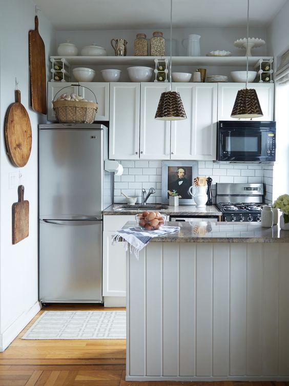 Cozinha decorada com prateleiras para utensílios e ganchos para tábuas de madeira.