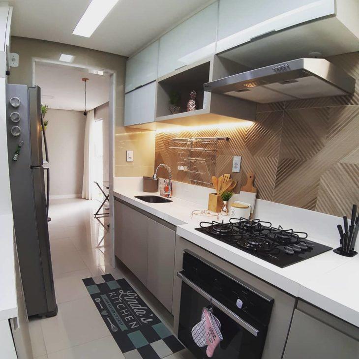 Cozinha com revestimentos em cores pasteis e tapete decorativo.