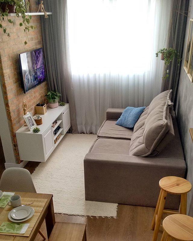 Sala decorada com televisão fixa na parede, vasos de planta suspensos e na mobília e parede de tijolos à vista.