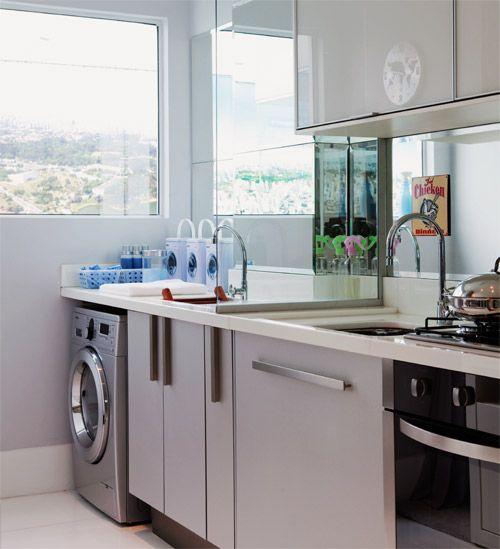 Cozinha e lavanderia divididas por uma parede de vidro.