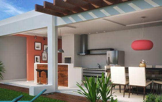 Área gourmet equipada com churrasqueira e eletrodomésticos além de sala de jantar.
