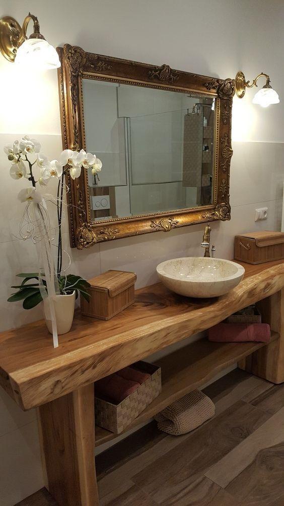 Banheiro com móvel de madeira rústica  e espelho com adornos.