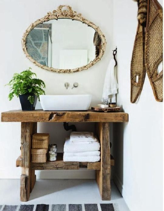 Banheiro com madeira rústica e espelho oval.