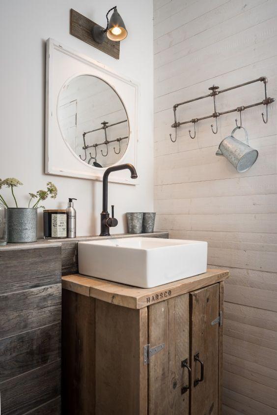 Banheiro com armário em madeira e cuba de apoio quadrada.