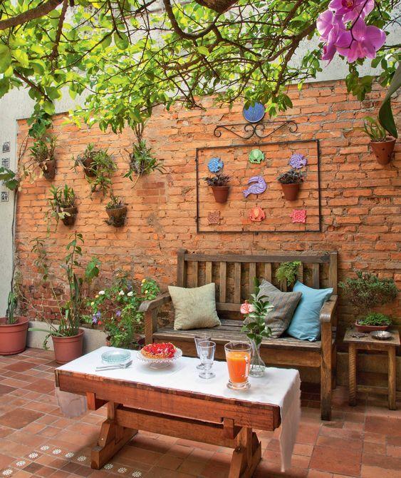 Jardim rústico traz móveis de madeira e parede de tijolo.