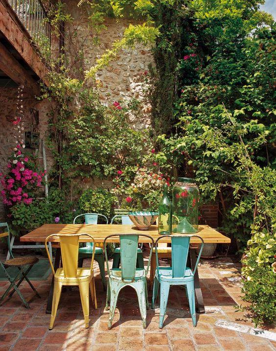 Jardim com mesa e cadeiras com visual rústico.