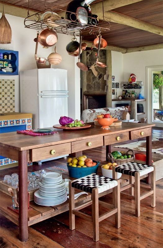 Cozinha traz ilha em madeira rústica.