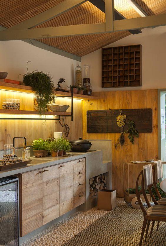 Cozinha moderna traz bancada e painel de madeira rústica.