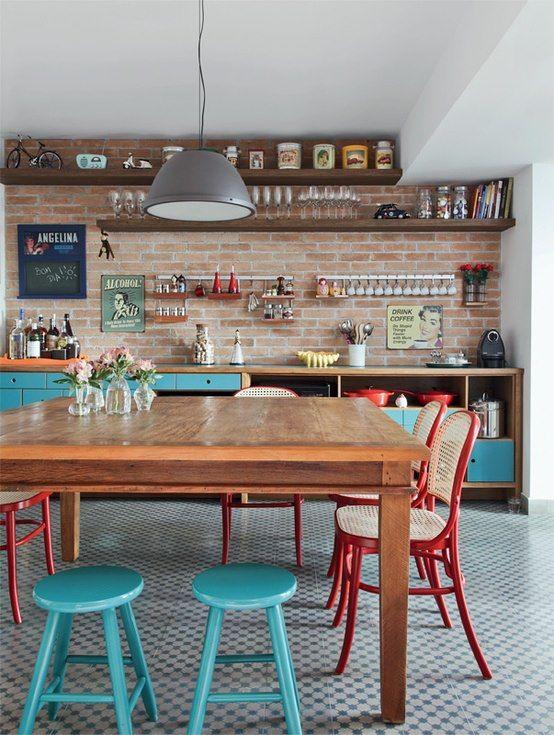 Cozinha com móveis rústicos traz cadeiras vermelhas em palinha e portas em azul.