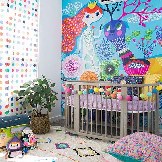 quarto de bebê com parede pintada a mão.