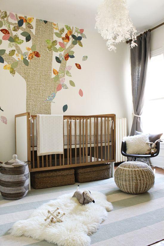 quarto de bebê com tons neutros e árvore colorida.