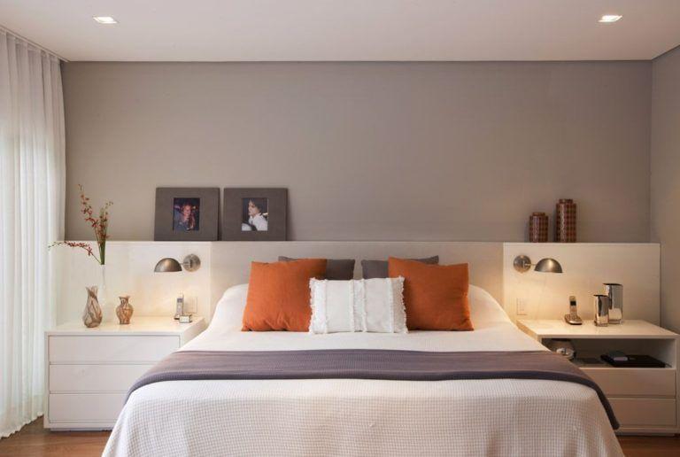 Quarto de casal planejado com decoração cinza e laranja.