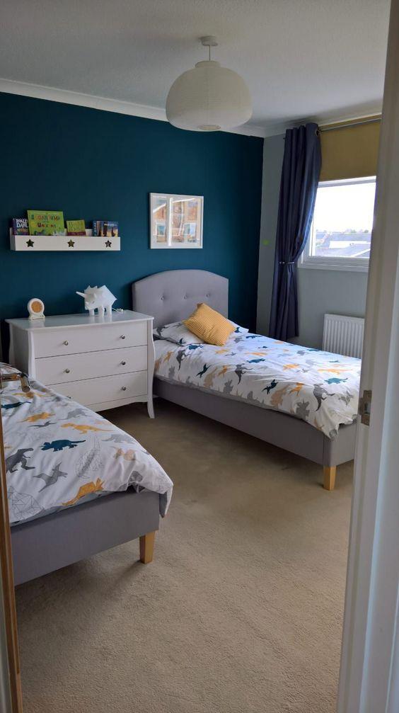 quarto de criança neutro com parede azul escuro