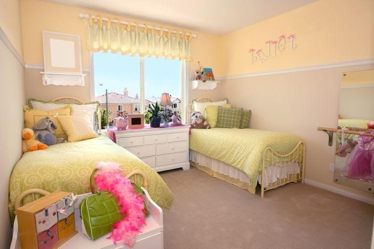 Quarto de menina amarelo com duas camas para irmãs.