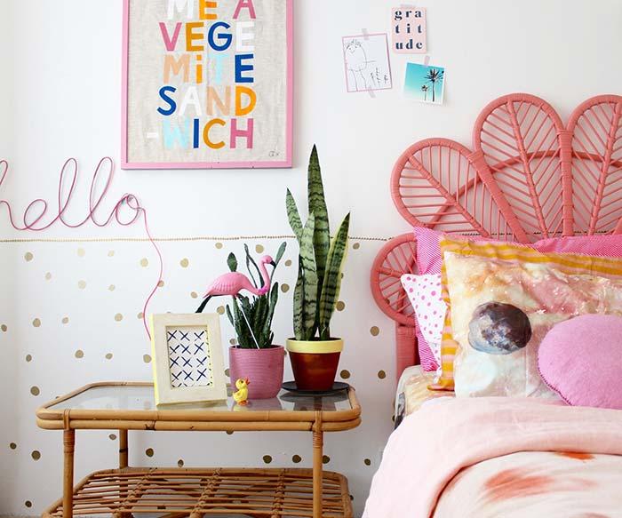 Criado-mudo de bambu e cabeceira de cama rosa.