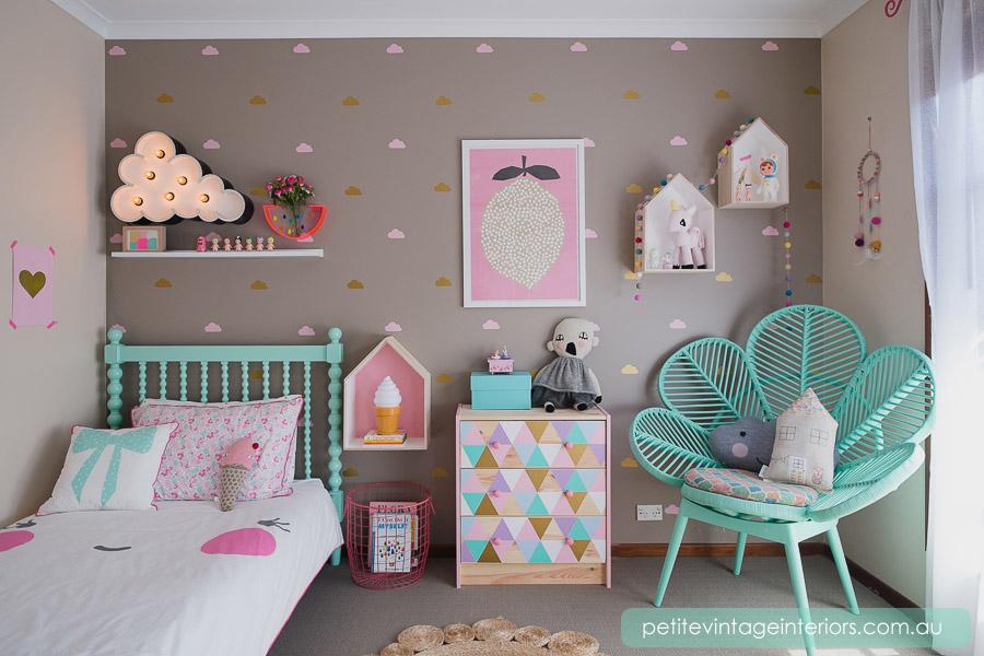 Decoração infantil com papel de parede de nuvens e cadeira decorada.