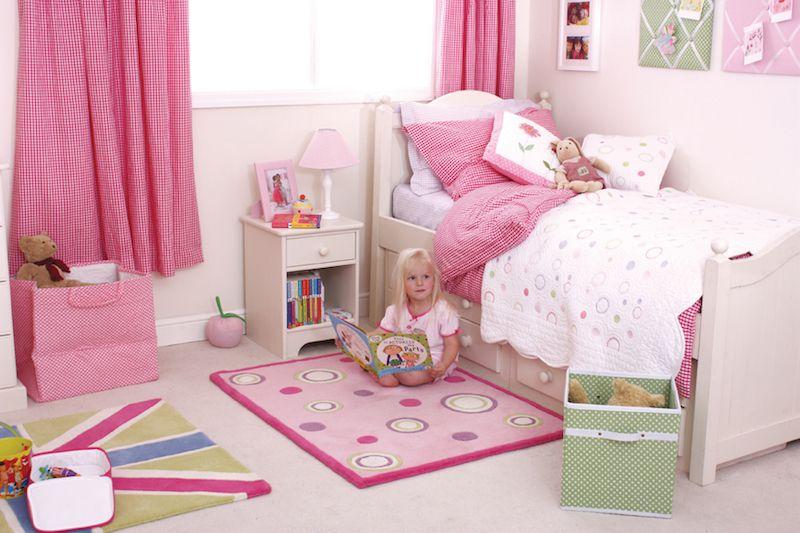 Decoração infantil rosa com tapete colorido.