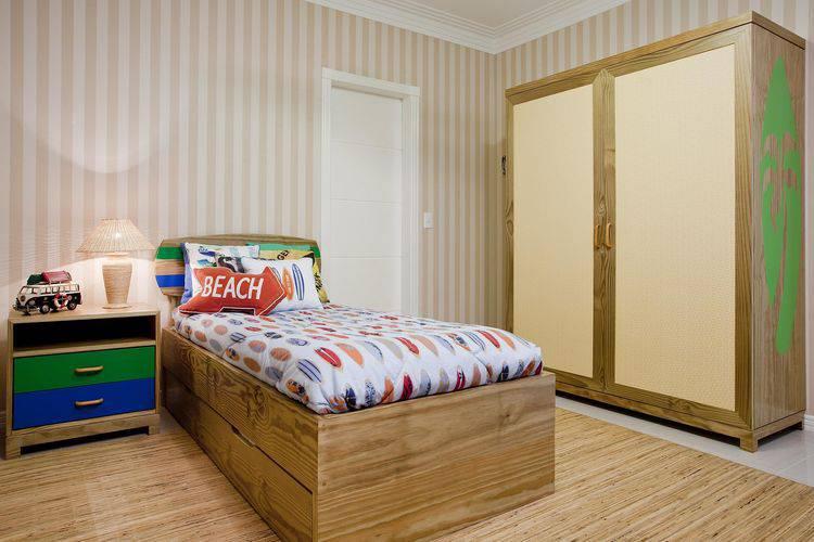 Quarto de menino com móveis de madeira e papel de parede listrado.