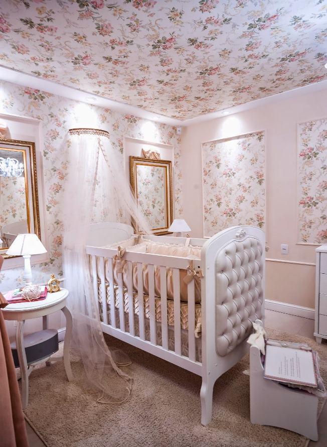 Quarto de bebê menina com papel de parede floral rosa.