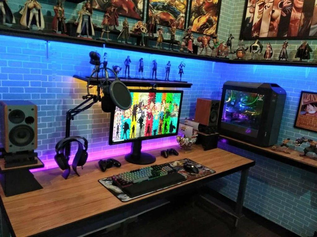 Setup gamer decorado com pôster e bonecos temáticos.
