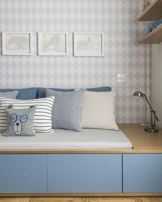 quarto de menino azul claro com papel de parede geométrico.