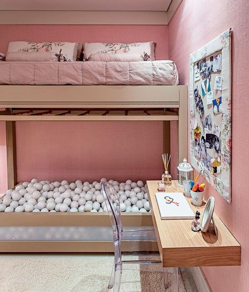 quarto infantil rosa com piscina de bolinha e mesa de estudos