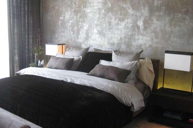 Quarto moderno com parede de cimento queimado e decoração luxuosa.
