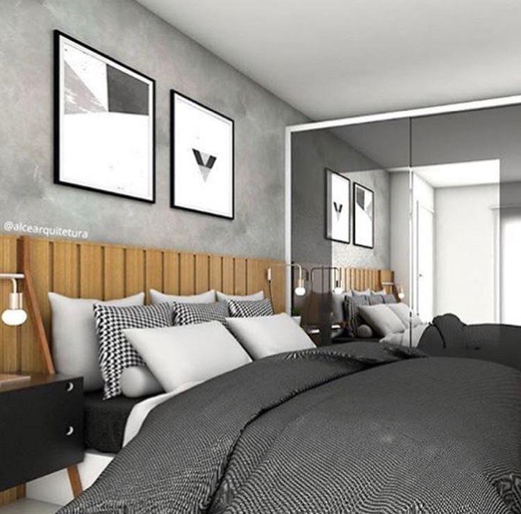 Decoração com parede de cimento queimado e cabeceira de cama em madeira.