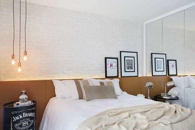 Quarto moderno com parede de tijolinho branco.