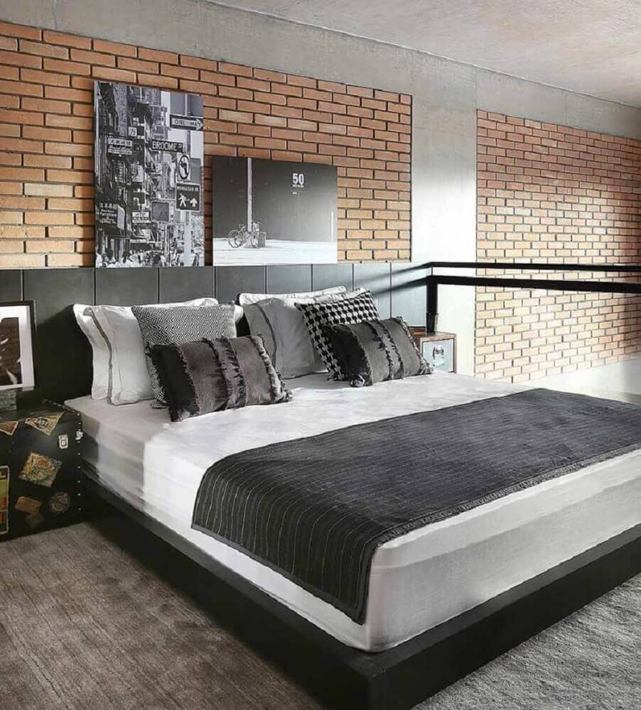 Quarto moderno com decoração de tijolinho aparente e cabeceira de cama preto.