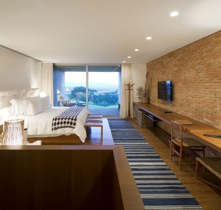 Quarto  moderno com decoração rústica e parede de tijolinho aparente.