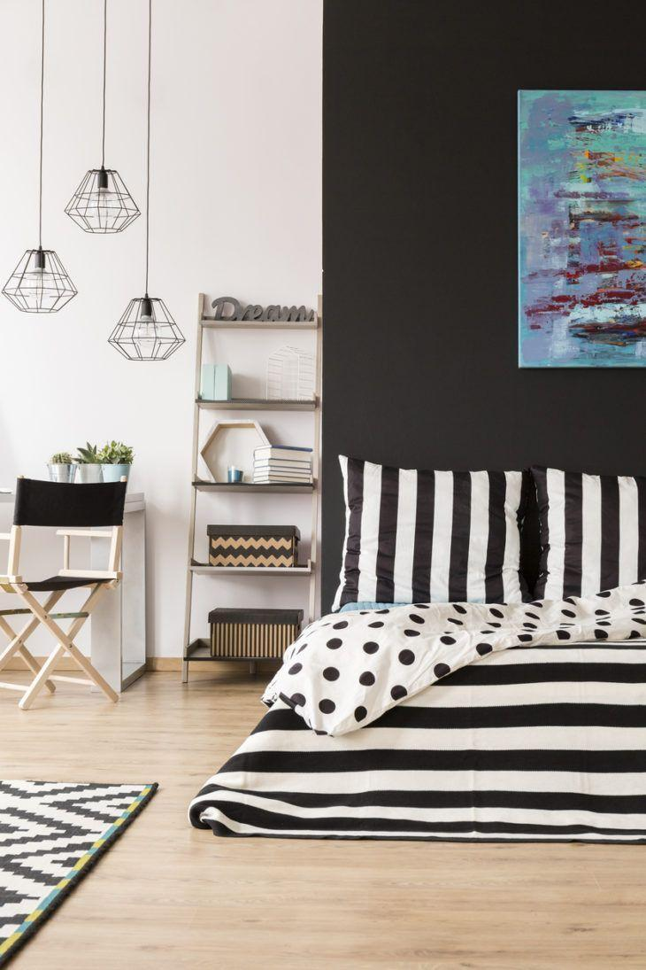 Quarto preto e branco decorado com listras e estampa de bolinha.