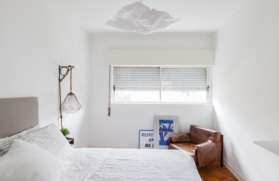 Quarto simples branco com lustre moderno.