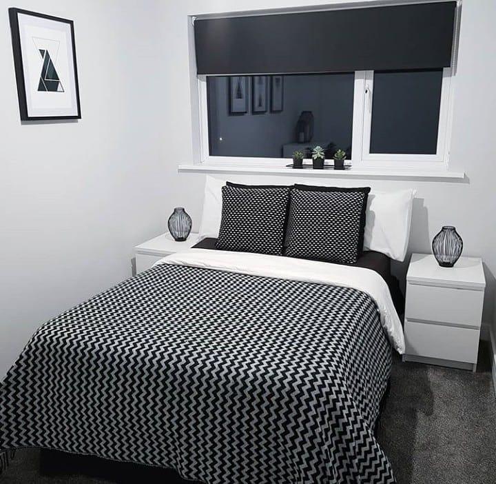 Quarto preto e branco com decoração simples.