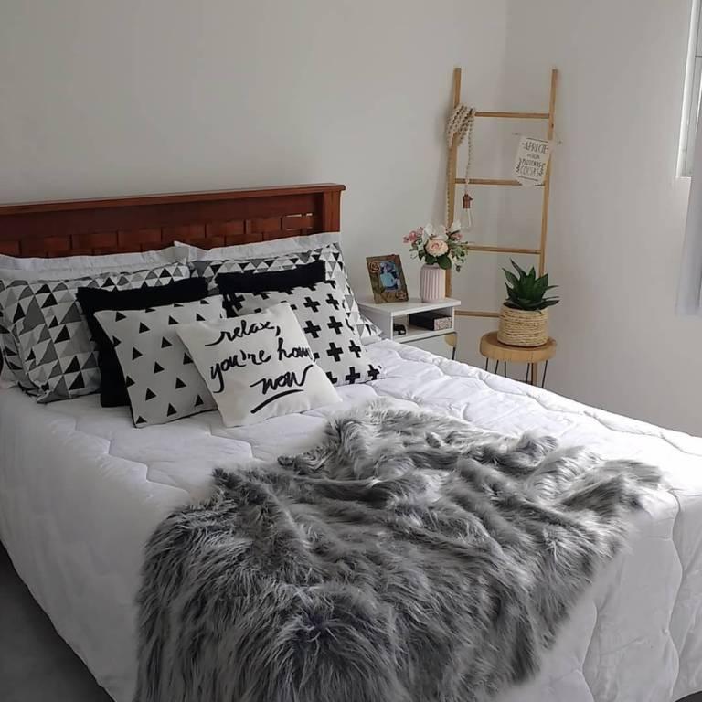 Quarto branco com decoração minimalista.