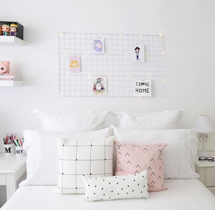 Quarto branco com decoração simples e mural de grade.