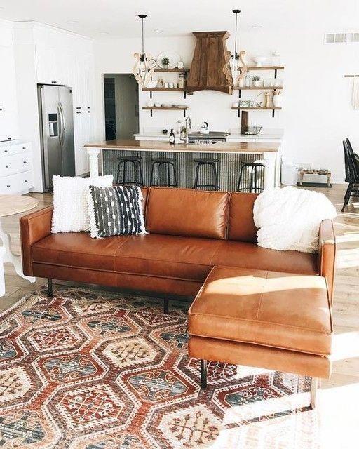 Sala de estar integrada com cozinha e sofá de couro marrom.