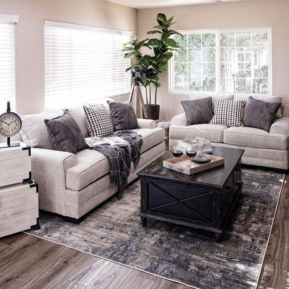 Sala de estar decorada em tons difentes tons de cinza.
