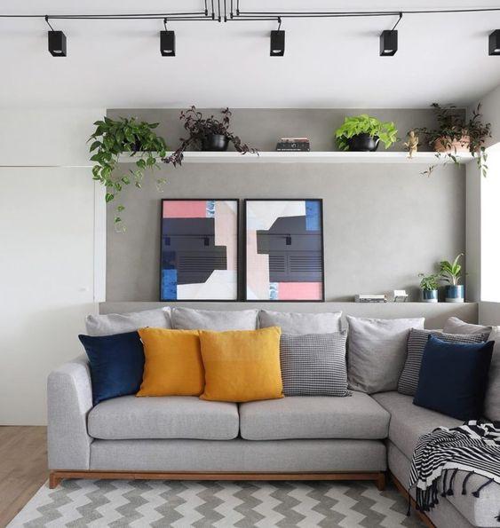 Sala com almofadas simples em azul, mostarda e listradas em preto e branco.
