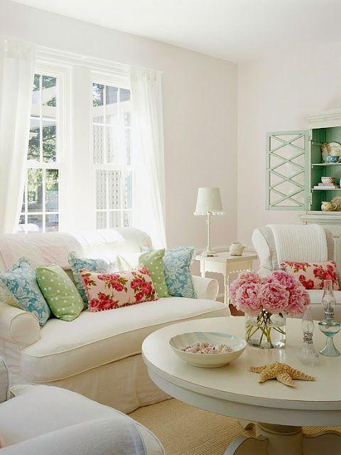 Sala decorada com sofá e poltronas brancas com almofadas coloridas.