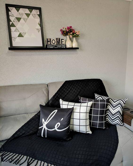 Sala com sofá com quatro almofadas em preto e branco.