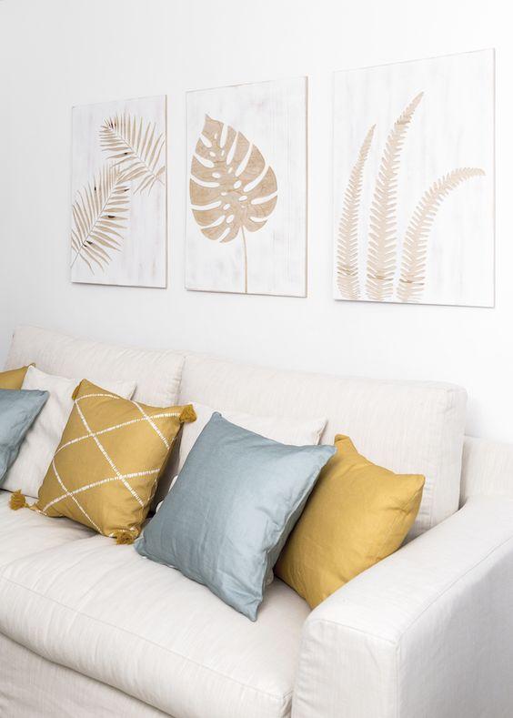 Sala com sofá branco com almofadas em branco, prata e dourado.
