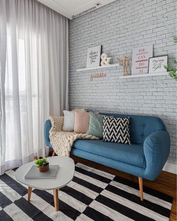 Sala com sofá azul, tapete preto e branco e almofadas coloridas.