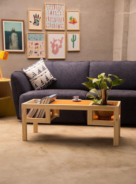 Sala de estar decorada com pequena mesa de centro feita de madeira com fundo laranja.
