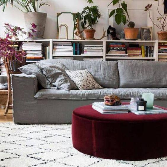 Sala de estar decorada com sofá cinza e mesa de centro redonda e vinho.